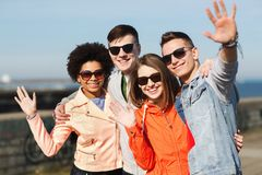 Happy teenage friends in shades waving hands Royalty Free Stock Photos