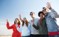 Happy teenage friends in shades waving hands Stock Photos
