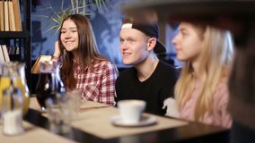 Happy teenage friends sitting and chatting in cafe stock footage