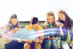 Happy teenage friends with smartphones outdoors Stock Photo