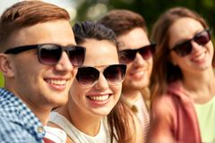 Happy teenage friends in sunglasses outdoors stock photography