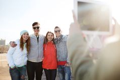 Happy teenage friends with tablet pc photographing Royalty Free Stock Photo