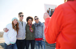Happy teenage friends with tablet pc photographing Royalty Free Stock Photos