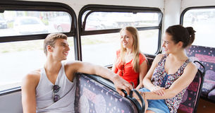 Happy teenage friends traveling by bus. Friendship, travel, vacation, summer and people concept - group of happy teenage friends traveling by bus and laughing Royalty Free Stock Photography