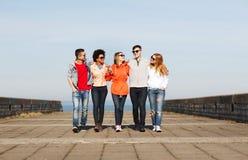 Happy teenage friends walking along city street Royalty Free Stock Photo
