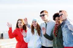 Happy teenage friends waving hands on city street Royalty Free Stock Image