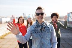 Happy teenage friends waving hands on city street Stock Photos