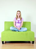 Happy Teenage Girl. A happy teenage girl sitting on a green sofa stock images