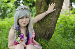 Happy teenage Girl. An image of a happy teenage girl thinking while holding flowers Stock Photo