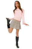 Happy teenage girl. Teenage girl in short skirt standing on one leg, isolated on white backgroung royalty free stock photo