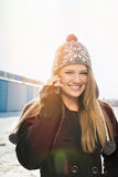 Happy teenage girl with beanie hat talking on the phone Stock Images
