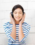 Happy teenage girl in big headphones Stock Images