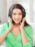 Happy teenage girl in big headphones Stock Images
