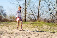 Happy teenage girl, blonde is walking barefoot with flying disk Royalty Free Stock Photos