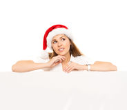 Happy teenage girl in a Christmas hat holding a large banner. Young and attractive teenage girl in a Christmas hat with a blank billboard isolated on white Royalty Free Stock Image
