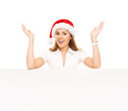 Happy teenage girl in a Christmas hat holding a large banner Stock Photo