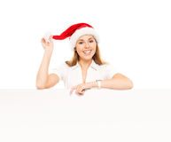 Happy teenage girl in a Christmas hat holding a large banner. Young and attractive teenage girl in a Christmas hat with a blank billboard isolated on white Royalty Free Stock Photography