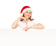 Happy teenage girl in a Christmas hat holding a large banner. Young and attractive teenage girl in a Christmas hat with a blank billboard isolated on white Stock Images