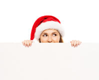 Happy teenage girl in a Christmas hat holding a large banner. Young and attractive teenage girl in a Christmas hat with a blank billboard isolated on white Stock Photo