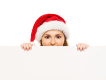 Happy teenage girl in a Christmas hat holding a large banner. Young and attractive teenage girl in a Christmas hat with a blank billboard isolated on white Royalty Free Stock Photos