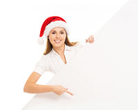 Happy teenage girl in a Christmas hat holding a large banner. Young and attractive teenage girl in a Christmas hat with a blank billboard isolated on white Royalty Free Stock Images