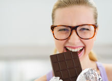 Happy teenage girl eating chocolate bar Stock Images
