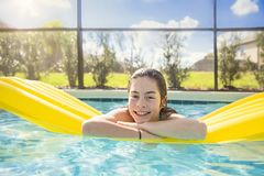 Happy Teenage girl floating in an outdoor swimming pool Royalty Free Stock Photo