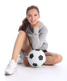 Happy teenage girl football player sits with ball Stock Photos