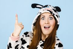Woman wearing pajamas cartoon pointing up. Happy teenage girl in funny nightclothes, pajamas cartoon style pointing up with positive surprised face expression Stock Photo