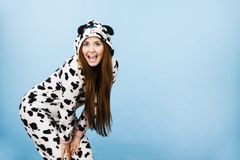 Woman wearing pajamas cartoon smiling. Happy teenage girl in funny nightclothes, pajamas cartoon style smiling, positive face expression, studio shot on blue Royalty Free Stock Photos