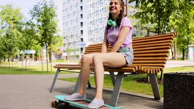 Happy teenage girl with headphones and longboard. Lifestyle, leisure and people concept - smiling young woman or teenage girl with headphones and longboard stock video