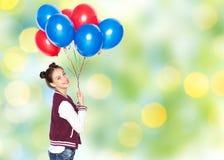 Happy teenage girl with helium balloons Stock Image