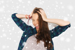 Happy teenage girl holding to head over snow. Winter, christmas, people, hair care, style and teens concept - happy pretty teenage girl holding to head over gray Royalty Free Stock Photos