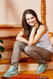 Happy teenage girl at home. Portrait of a beautiful teenage girl with long brown hair, sitting on stairs at home, smiling into camera Stock Photo