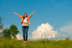 Happy teenage girl jumping on the summer outdoors background Stock Image