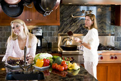 Happy teenage girl in kitchen with mother stock photo