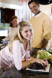 Happy teenage girl in kitchen with parents stock photography