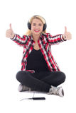 Happy teenage girl listening music in earphones and thumbs up is Royalty Free Stock Photo
