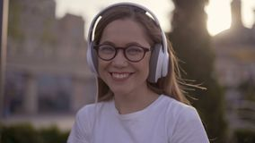 Happy teenage girl listening to music on headphones in park in summer. 4K stock video footage