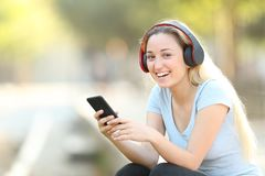 Happy teenage girl listening to music looking at camera stock photos