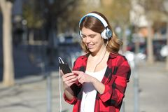 Happy teenage girl listening to music walking outdoors royalty free stock photos