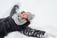 Happy teenage girl lying in the deep snow Stock Images