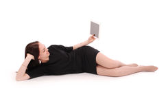 Happy teenage girl lying on the floor with tablet pc Royalty Free Stock Images