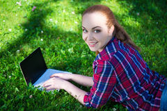 Happy teenage girl lying with laptop on grass in park Royalty Free Stock Images