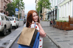 Happy teenage girl made a purchase. And go through the city streets with packages. The girl has red hair and freckles Stock Image