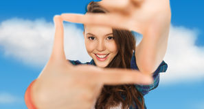 Happy teenage girl making frame of fingers Stock Photography