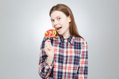 Happy teenage girl in plaid shirt standing and eating lollipop Stock Image