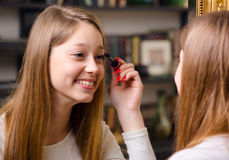 Happy teenage girl putting make up Stock Image