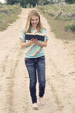 Happy teenage girl reading a book while walking down a dirt road Stock Photos