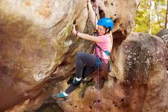 Happy teenage girl rock climbing in forest area. Happy teenage girl in helmet rock climbing in forest area stock image